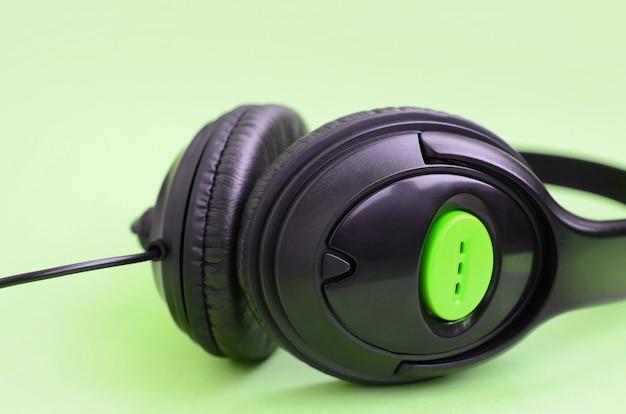 Music listening concept. black headphones lies on green background