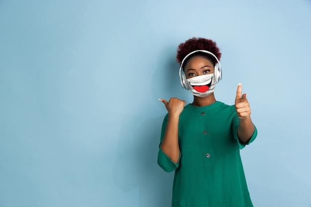Прослушивание музыки. портрет молодой девушки с эмоциями на ее маске для лица