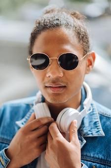 音楽愛好家。音楽を聴きに行く間、首にヘッドフォンを保持している陽気な若い男