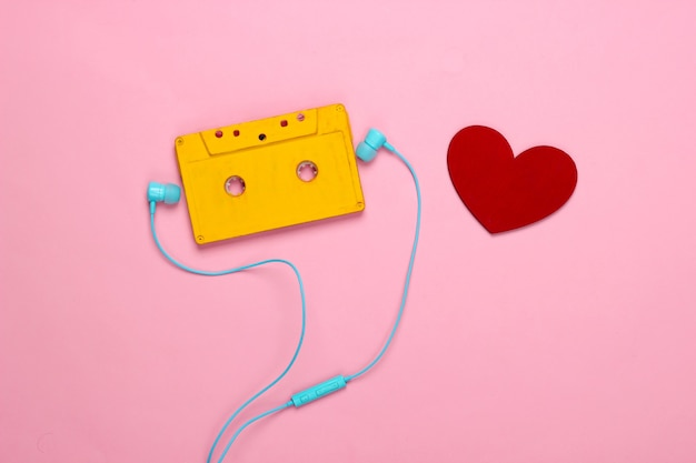 Music lover concept. audio cassette with earphones and heart on a pink