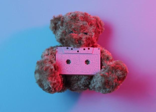 Music lover concept teddy bear hold audio cassette in red blue neon light.