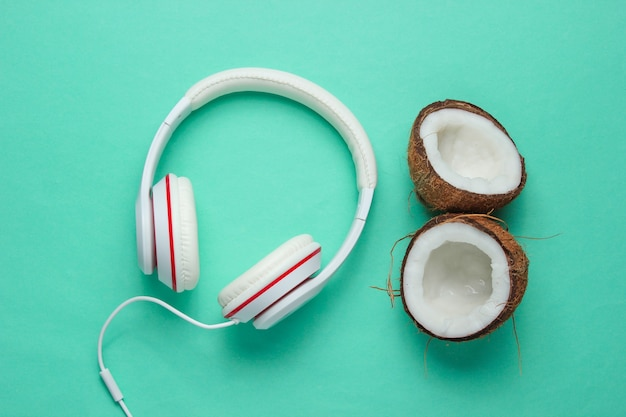 Music lover creative concept. summer background. white classic headphones, coconut halves on a blue background.