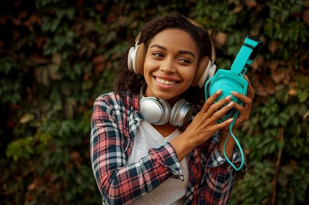 Меломан в наушниках, слушая музыку в летнем парке. женский аудиофил, прогулки на свежем воздухе, девушка в наушниках, зеленые кусты