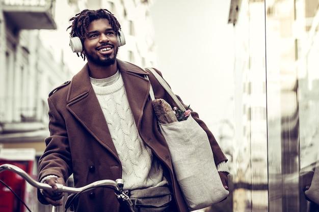 音楽愛好家。通りを歩きながら彼の顔に笑顔を保つ親切なブルネットの男