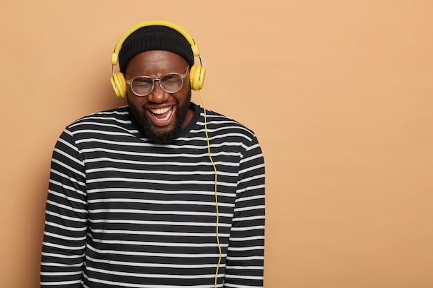 Music lover laughs happily while listens audio track in stereo headphones, wears big optical glasses and striped jumper