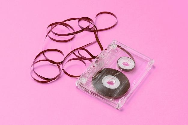 音楽愛好家のミニマリズムの概念。レトロなスタイルの80年代。ピンクの紙にフィルム付きのオーディオカセット