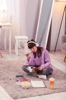 Любитель музыки. серьезная брюнетка девушка сидит на полу и читает книгу перед уроком