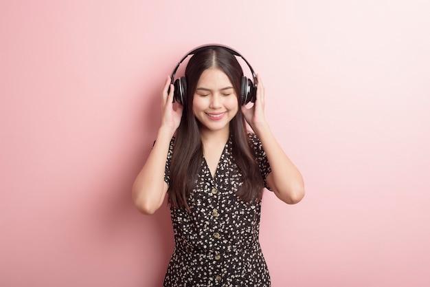 Любитель музыки женщина наслаждается с гарнитурой на розовом фоне