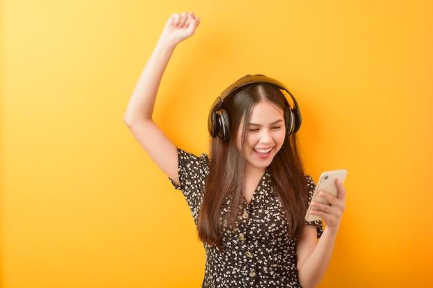 음악 연인 여자는 노란색 배경에 헤드셋과 함께 즐기고있다