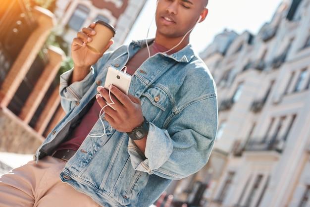 Молодой парень меломана в наушниках сидит на улице города, слушая музыку, держа чашку
