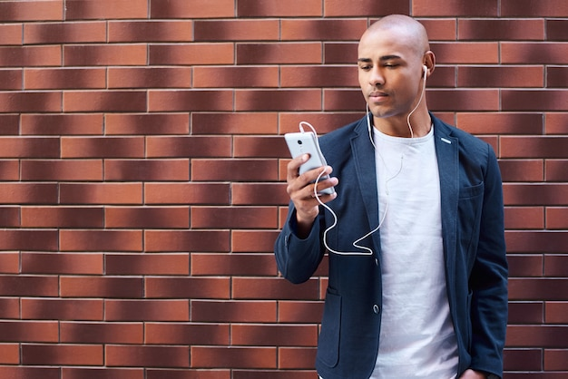 Music lover young guy wearing earphones standing on wall listening to music on smartphone serious