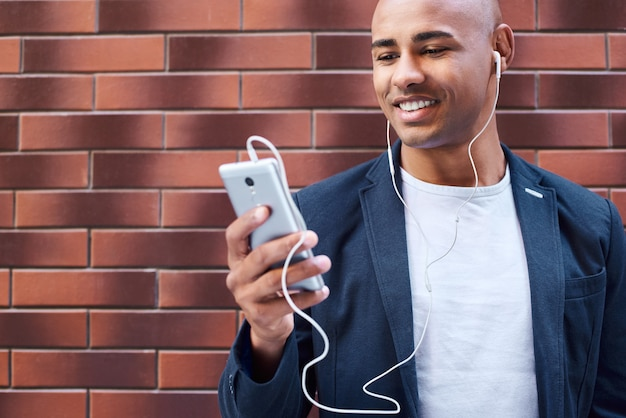 Music lover young guy wearing earphones standing on wall listening to music on smartphone smiling