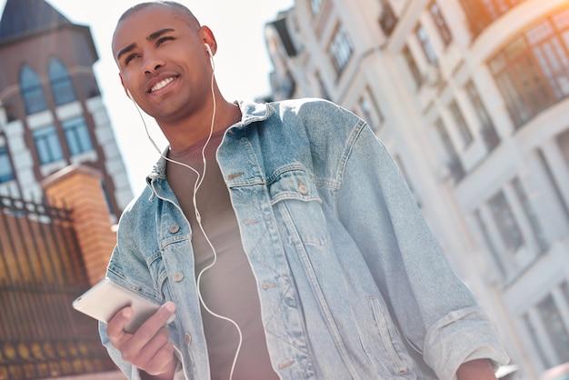 Молодой парень меломана в наушниках гуляет по улице города, слушая музыку, держа смартфон