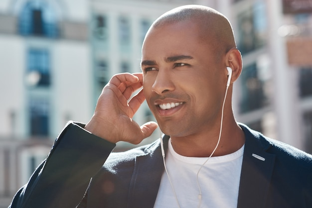 Music lover young man wearing headphones standing on the city street listening to music looking