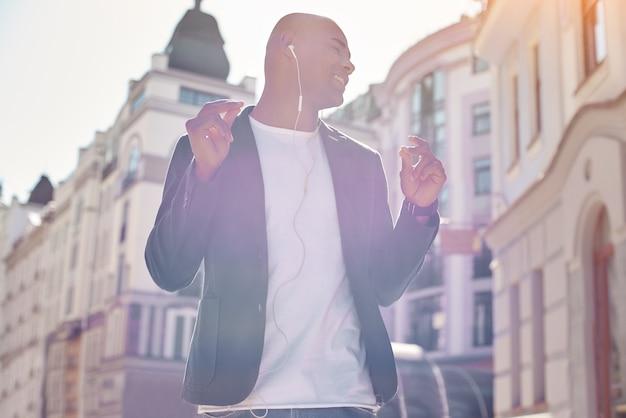 Молодой человек меломана в наушниках, стоящий на улице города, слушает музыку закрыто