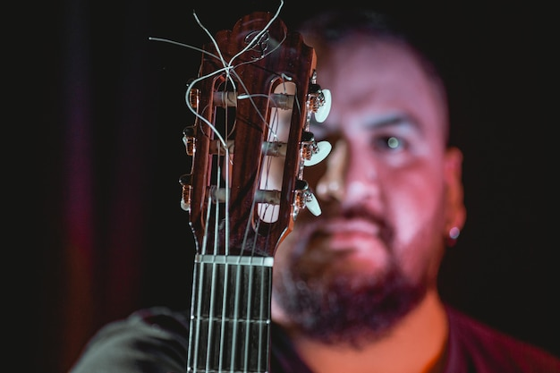 黒の背景でセットアップされた暗い場所でモデリングする音楽の男