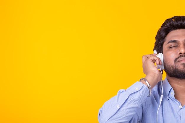 Концепция музыки, меломана и людей - счастливый индийский мужчина слушает музыку и наслаждается ею над желтой стеной с копией пространства.