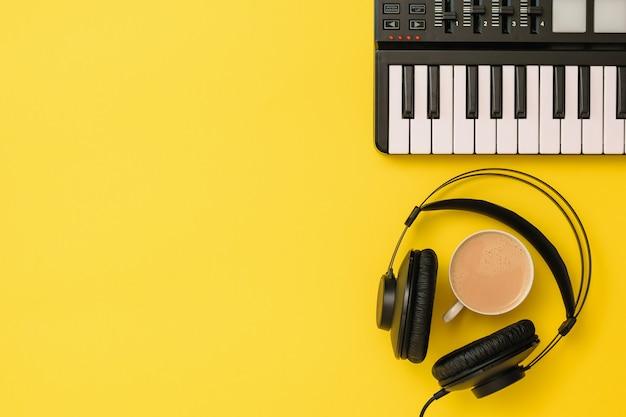 黄色の背景に音楽ミキサーと黒のヘッドフォンとコーヒー。音楽トラックを録音するための機器。上からの眺め。フラットレイ。