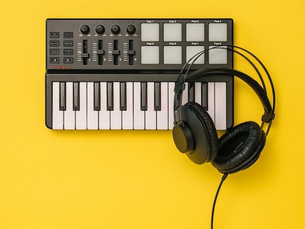 黄色の背景に音楽ミキサーと黒のヘッドフォン。音楽トラックを録音するための機器。上からの眺め。フラットレイ。