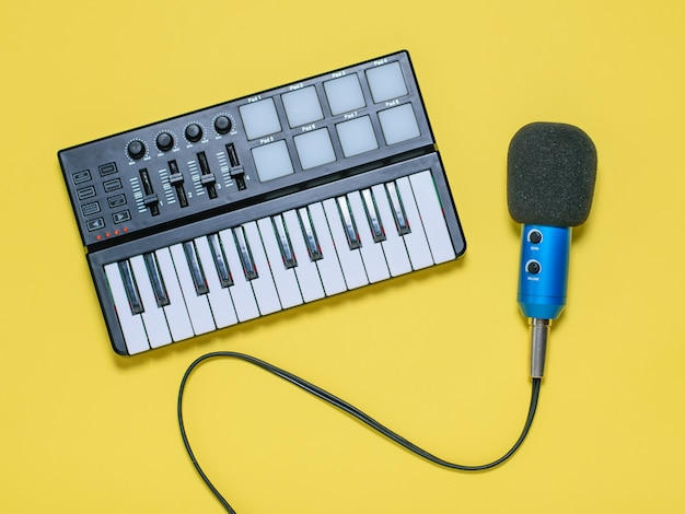 Music mixer and blue microphone with wires on yellow surface. the view from the top.