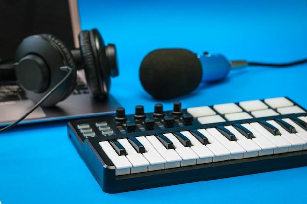 Музыкальный микшер, ноутбук и синий микрофон с проводами на синей поверхности. оборудование для записи музыкальных треков.