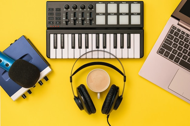Music mixer,microphone, headphones and sound card on yellow background. the concept of workplace organization. equipment for recording, communication and listening to music.