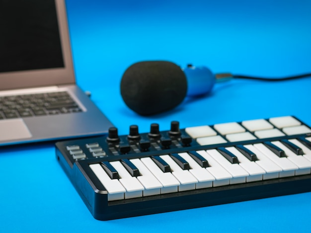 Music mixer, open laptop and microphone with wires on blue