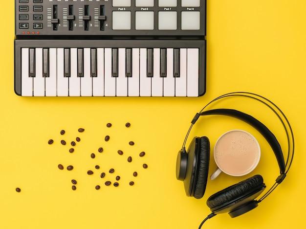 ミュージックミキサー、散らばったコーヒー豆、ヘッドフォン、黄色の背景に一杯のコーヒー。音楽トラックを録音するための機器。上からの眺め。フラットレイ。