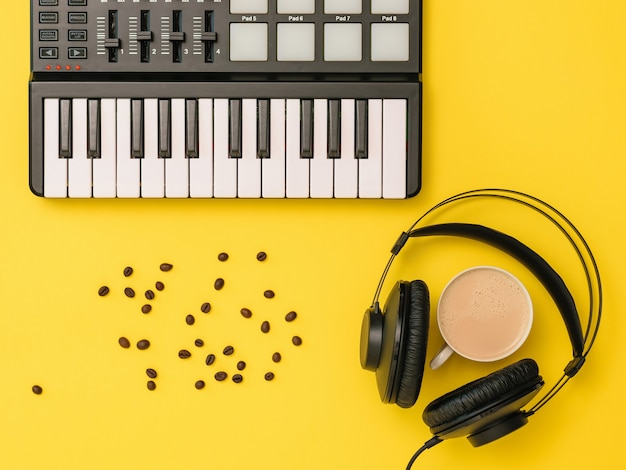 Music mixer, scattered coffee beans, headphones and a cup of coffee on a yellow background. equipment for recording music tracks. the view from the top. flat lay.