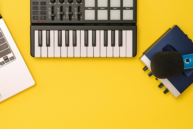 Music mixer, sound card, laptop and microphone on yellow