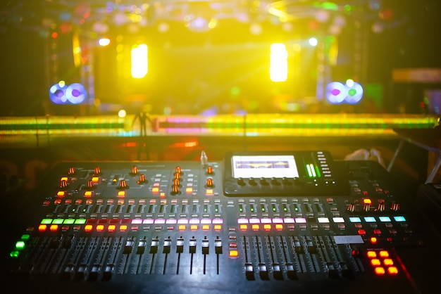 Music mixer with stage, concert background blurred, yellow light