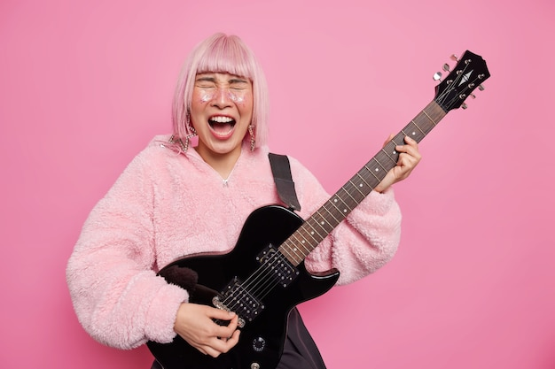 Music music intstruments and hard rock concept. emotional hipster girl exclaims loudly keeps mouth opened plays black acoustic guitar wears fur coat
