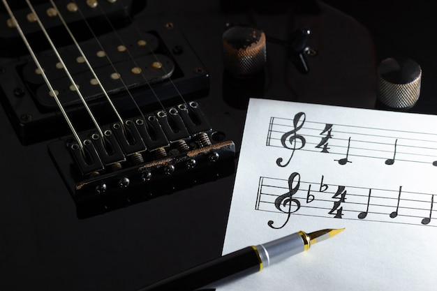 Music note and vintage pen on black electric guitar in darkness. concept of rock music creative.
