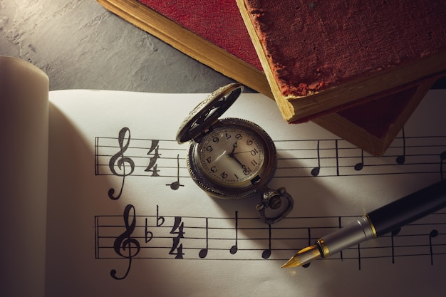 Music notes and old book with pocket watch on wooden table in morning light.