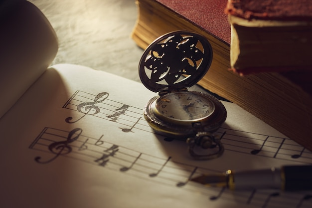 Music notes and old book with pocket watch on wooden table