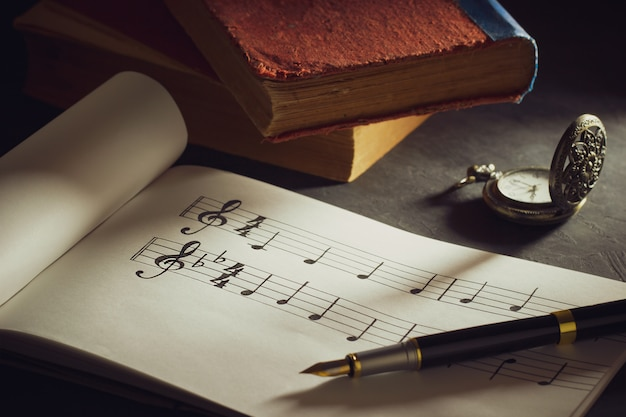 Music notes and old book with pocket watch on wooden table.