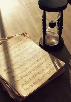 Music notes on papers and hourglass