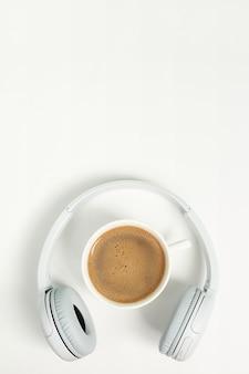 Концепция музыки или подкаста с наушниками и чашкой кофе. вид сверху, плоская планировка