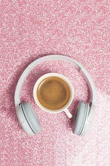 Концепция музыки или подкаста с наушниками и чашкой кофе, вид сверху