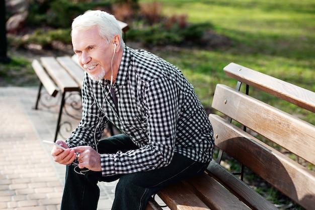 Музыка на открытом воздухе. энергичный старший мужчина отдыхает на скамейке и слушает музыку