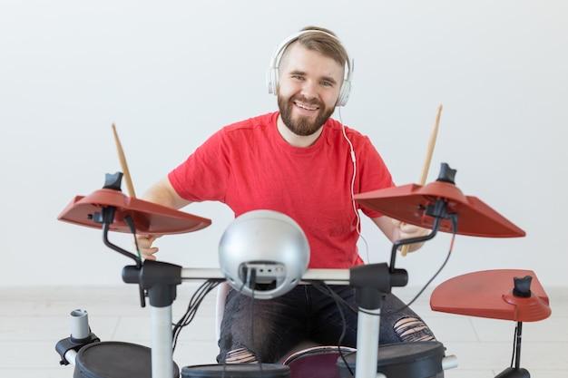 音楽、人、趣味のコンセプト-ドラムを演奏する男性ドラマーは非常に感情的なように見えます