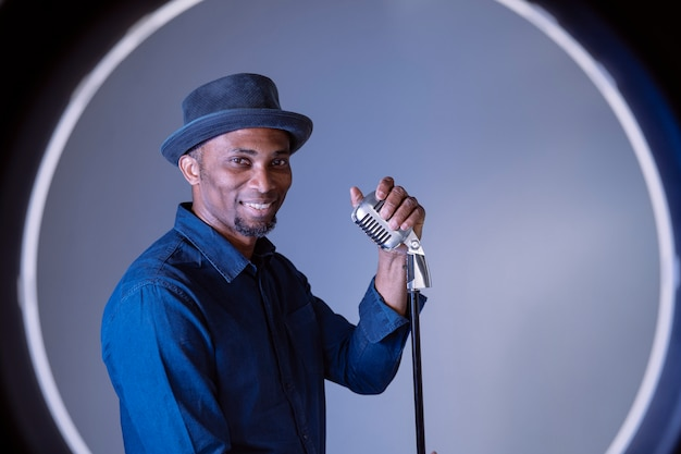 Music performer singing a song with a vintage silver microphone. ethnic afro man performing old music industry. african american blues male singer holding a professional mic. rhythm and blues style.