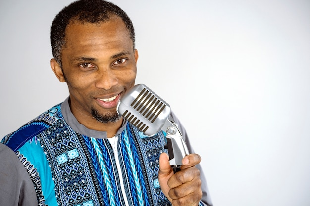 Music performer singing a song with a vintage silver microphone. ethnic afro man performing old music industry.