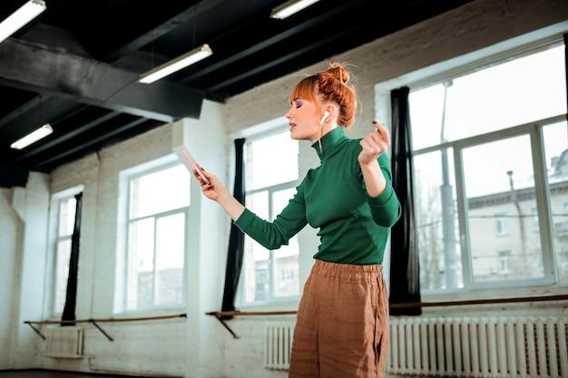 Музыка. рыжий профессиональный инструктор по йоге с пучком волос слушает музыку во время джазовых танцев