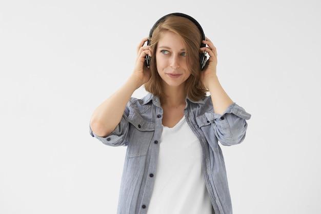 音楽、リラクゼーション、楽しいコンセプト。ワイヤレスヘッドフォンを介して良いジャズトラックを楽しんで、喜んで表情で目をそらし、白い上に青いシャツを着た美しい現代の女の子の孤立した写真