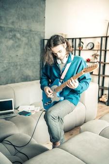 Повторение музыки. красивый артистичный молодой парень, будучи воображаемой звездой музыки, выступает с гитарой дома