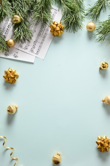 Music sheets for christmas carols and sings decorated golden balls on blue background
