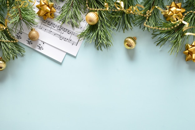 Music sheets for christmas carols and sings decorated golden balls on blue