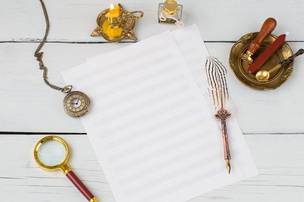 Музыкальные листы, авторучка, карманные часы на деревянном столе