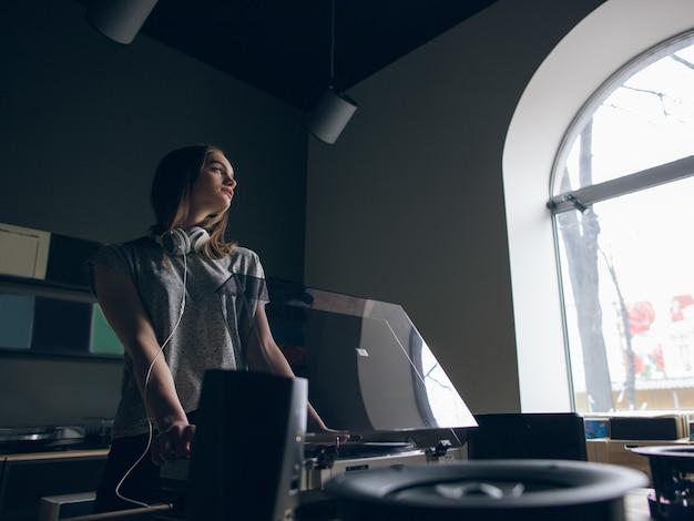 음악 가게. 사려 깊은 소녀는 비닐 레코드를 선택합니다. 차분한 분위기의 장소, 창의적인 분위기